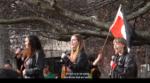 Ngā Hinepūkōrero video still from BLM rally NZ June 2020. Three people on stage doing spoken word into microphones. Tinorangatiratanga flag in the background.
